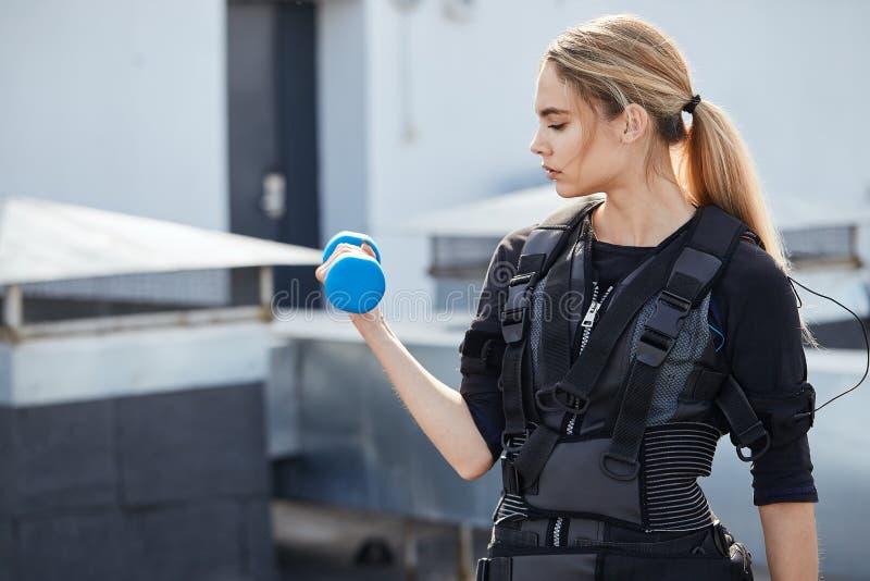 Menina atrativa da aptidão no terno muscular elétrico que faz o exercício para os braços imagens de stock royalty free