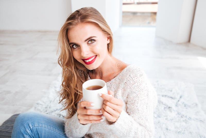 Menina atrativa de sorriso na camiseta que guarda o copo de chá foto de stock royalty free