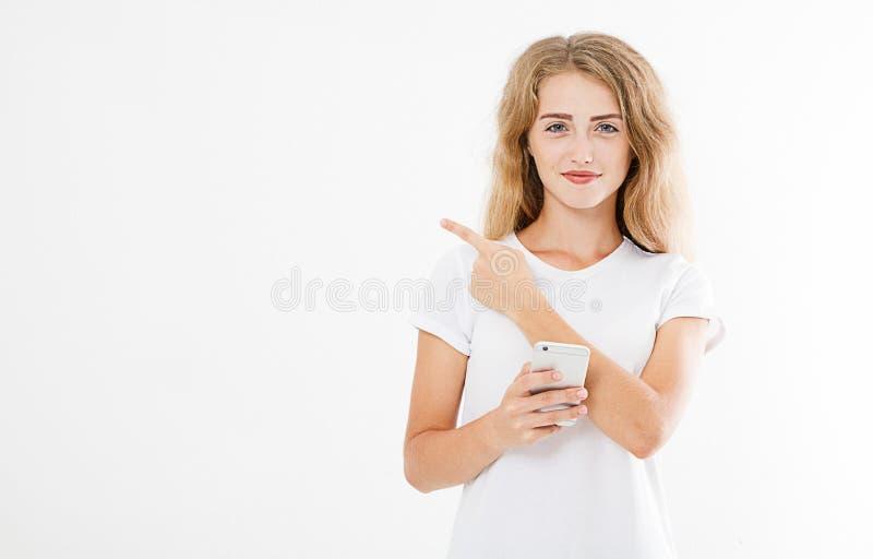 A menina atrativa de sorriso, telefone celular da posse da mulher apontando o dedo isolado no fundo branco, mão que guarda o tele fotografia de stock royalty free