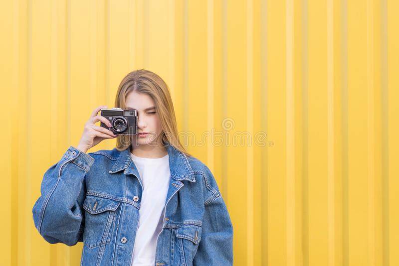 Menina atrativa do hipist fotografada em uma câmera do filme em um fundo amarelo imagem de stock