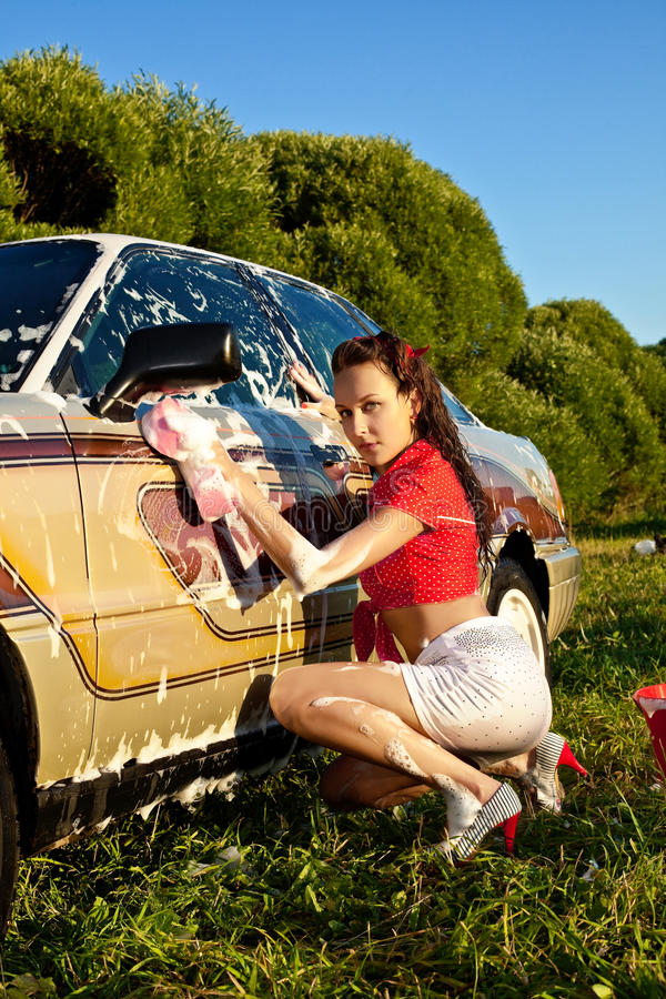 Menina atrativa do pinup que lava um carro no verão imagem de stock royalty free