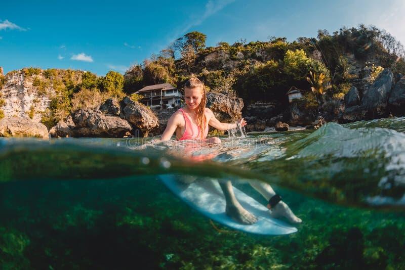 Menina atrativa do surfista com prancha O surfista senta-se na placa no oceano foto de stock