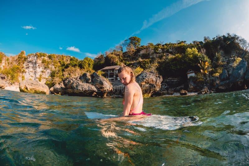 Menina atrativa do surfista com prancha O surfista senta-se na placa no oceano imagens de stock