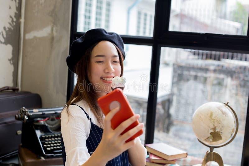 Menina atrativa e à moda asiática que come o gelado e que toma um tiro da foto do selfie fotografia de stock royalty free