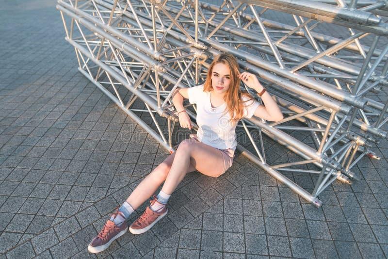menina atrativa em um t-shirt branco que senta-se no pavimento e que olha a câmera imagem de stock royalty free
