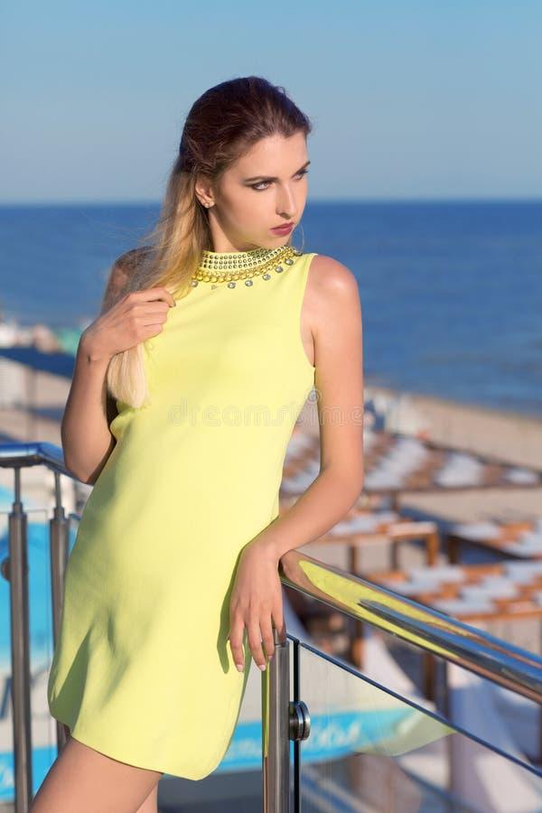 Menina atrativa em um vestido amarelo curto no fundo de um hotel confortável A menina elegante no fundo do mar fotos de stock