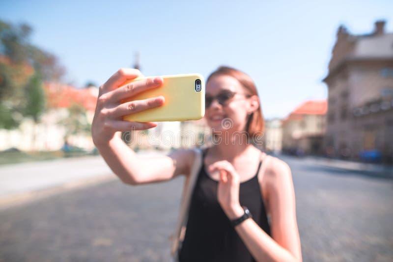 A menina atrativa em um vestido preto toma o selfie na rua da cidade velha Cidade velha de passeio em um dia de verão ensolarado fotografia de stock