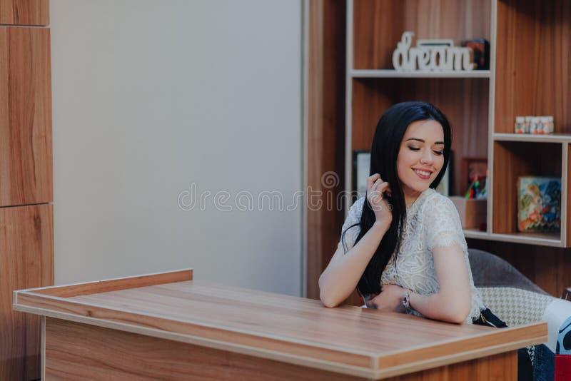Menina atrativa emocional nova que senta-se em uma mesa em um escrit?rio ou em um audit?rio moderno foto de stock royalty free