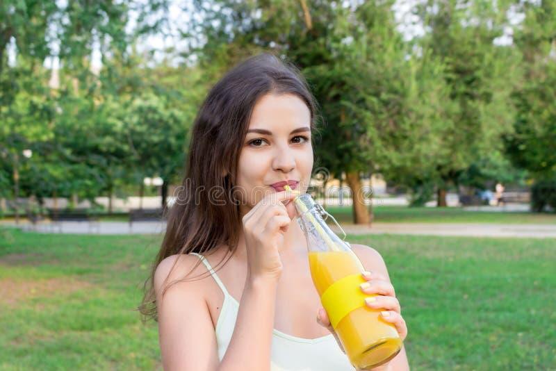 A menina atrativa está bebendo o suco fresco com o ar livre da palha A mulher bonita está guardando uma garrafa da limonada fria foto de stock