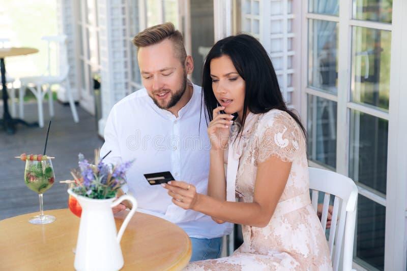 A menina atrativa está sentando-se em um café com seu homem, um par está olhando algo no Internet, usando uma tabuleta um homem imagens de stock royalty free