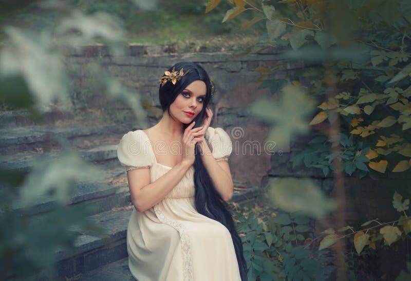 A menina atrativa lindo que afaga seu cabelo preto longo com ternura, senta-se nas etapas de pedra na floresta profunda, olha foto de stock
