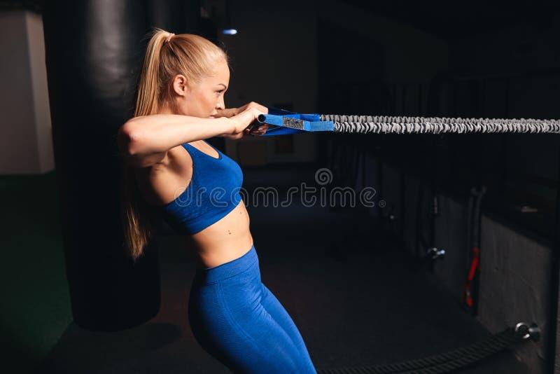 Menina atrativa magro 'sexy' que faz exercícios com a faixa do resestance do trx fotografia de stock royalty free