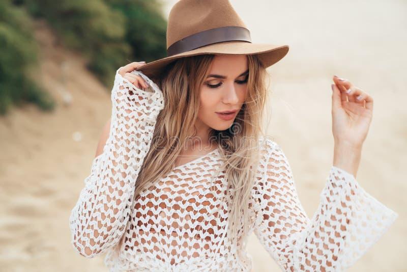 A menina atrativa no branco faz crochê o roupa de banho e o chapéu que têm o bom tempo na praia tropical da areia em férias de ve fotos de stock