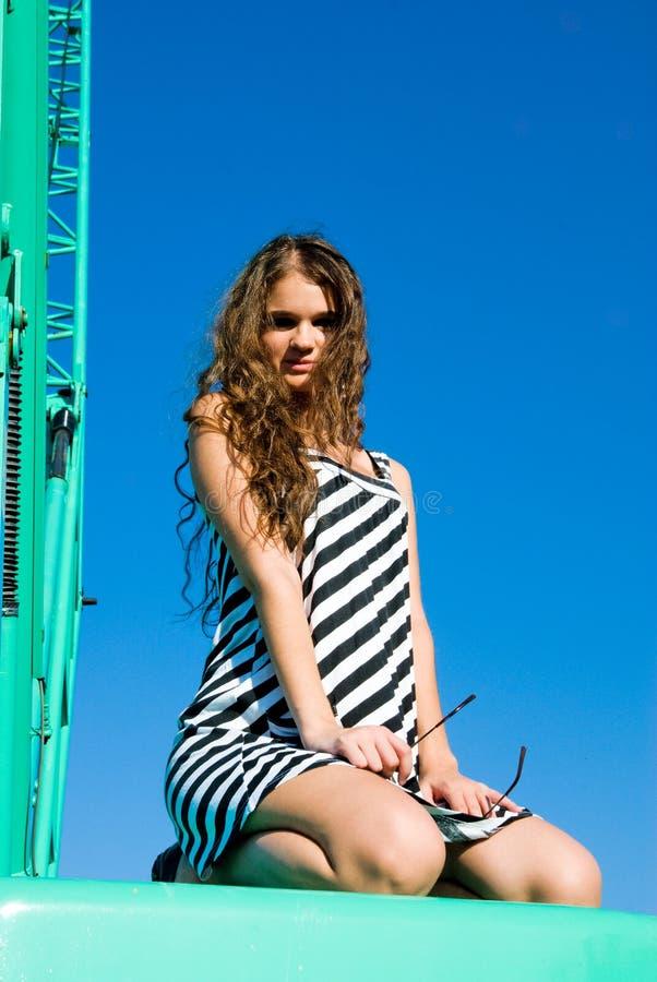 Menina atrativa no guindaste de construção foto de stock royalty free