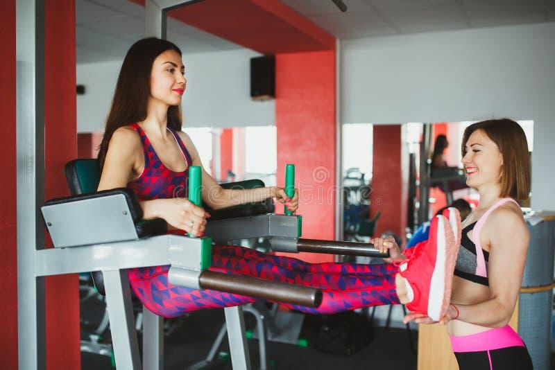 Menina atrativa nova com o instrutor pessoal no gym foto de stock royalty free