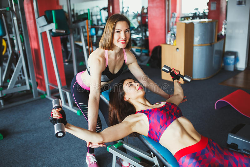 Menina atrativa nova com o instrutor pessoal no gym fotografia de stock royalty free