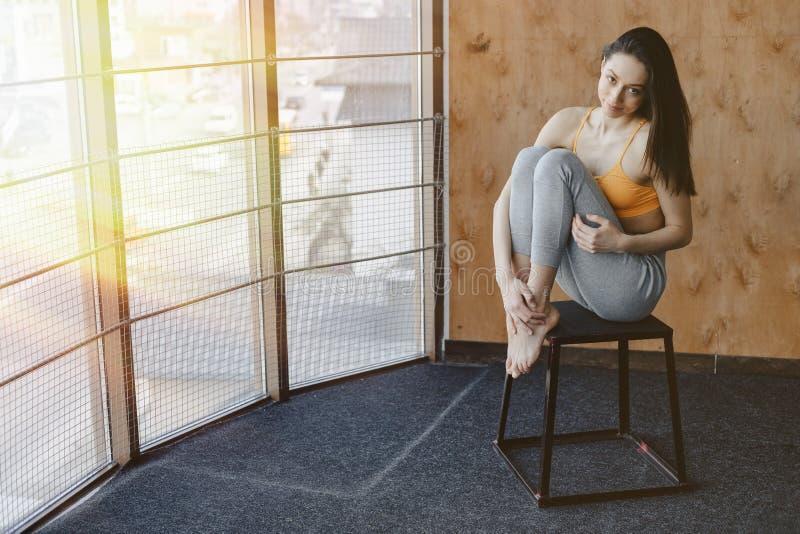 Menina atrativa nova da aptid?o que senta-se na cadeira perto da janela no fundo de uma parede de madeira, descansando em classes imagem de stock royalty free