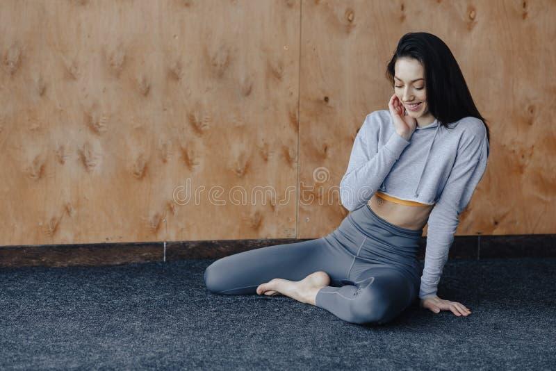 Menina atrativa nova da aptid?o que senta-se no assoalho perto da janela no fundo de uma parede de madeira, descansando em classe imagens de stock