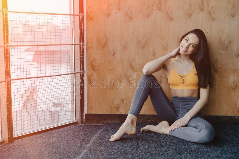 Menina atrativa nova da aptid?o que senta-se no assoalho perto da janela no fundo de uma parede de madeira, descansando em classe fotos de stock