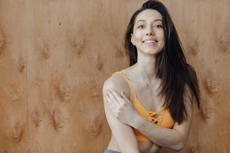 Menina atrativa nova da aptid?o que senta-se no assoalho perto da janela no fundo de uma parede de madeira, descansando em classe fotos de stock royalty free