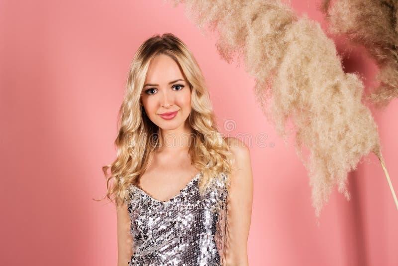 Menina atrativa nova do blondie que levanta em um vestido de prata brilhante em um estúdio da foto em um fundo cor-de-rosa imagens de stock royalty free