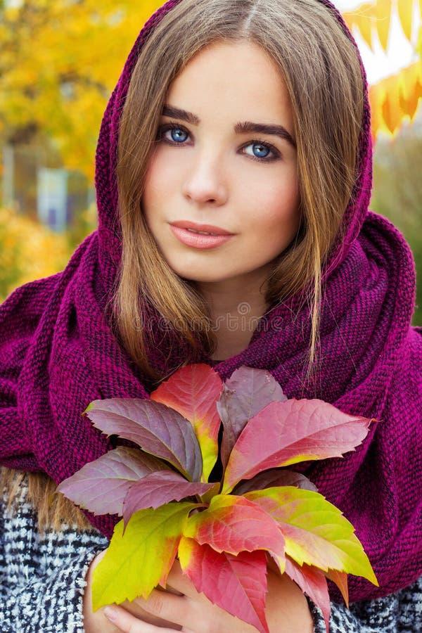 Menina atrativa nova encantador bonita com grandes olhos azuis com um lenço em sua cabeça, terra arrendada longa do cabelo escuro imagem de stock royalty free