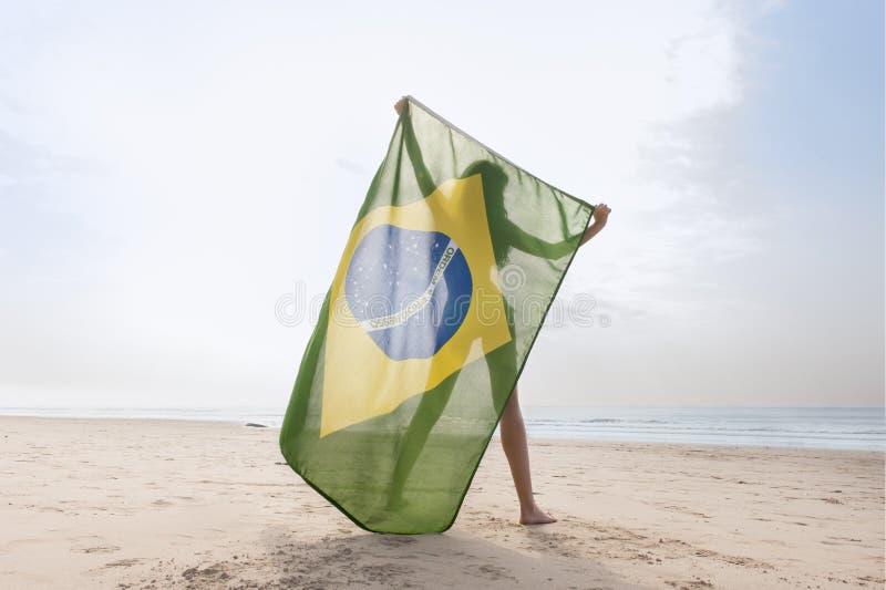 Menina atrativa nova na praia com bandeira de Brasil fotos de stock royalty free