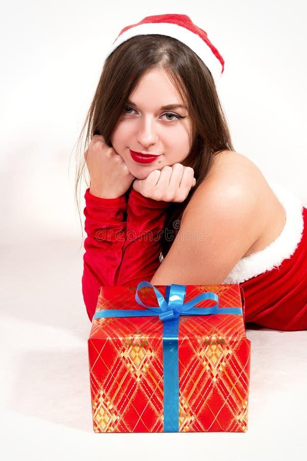 A menina atrativa nova no traje de Santa encontra-se ao lado de um presente, isolador imagens de stock royalty free