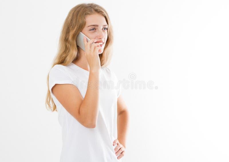 Menina atrativa nova que fala em um telefone celular em um espaço branco da cópia do t-shirt imagens de stock royalty free