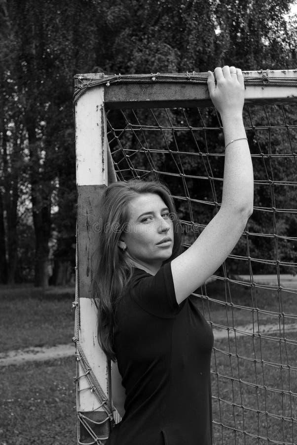 Menina atrativa nova que levanta no campo de futebol perto da porta foto de stock