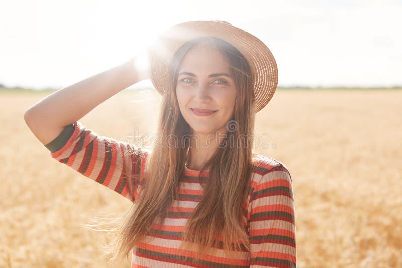 A menina atrativa nova que veste em chapéu listrado do vestido e de palha, estando no campo de trigo com spiklets, mantém sua mão imagens de stock