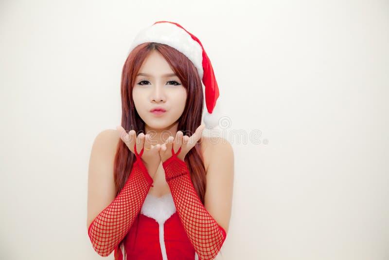 A menina atrativa nova veste o terno de Santa e o chapéu de Santa abre a palma de duas mãos e de estar no fundo branco imagem de stock royalty free