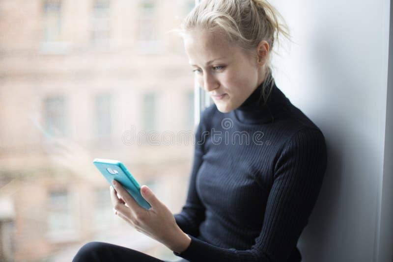 A menina atrativa olha o telefone e os sorrisos fotografia de stock royalty free