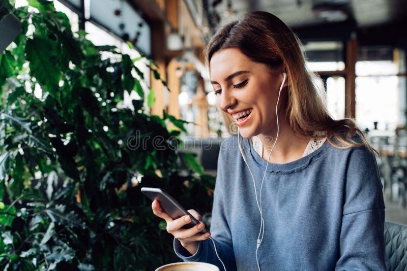 Menina atrativa que escuta a música nos auriculares no smartphone no café imagens de stock
