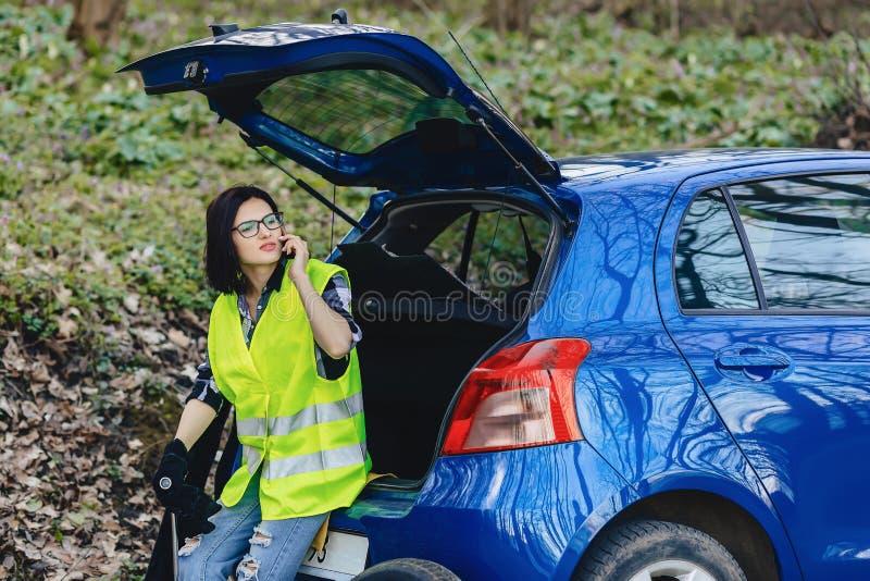 menina atrativa que fala pelo telefone perto do carro na estrada no jaque da segurança imagem de stock royalty free