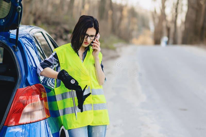 menina atrativa que fala pelo telefone perto do carro na estrada no jaque da segurança imagens de stock royalty free
