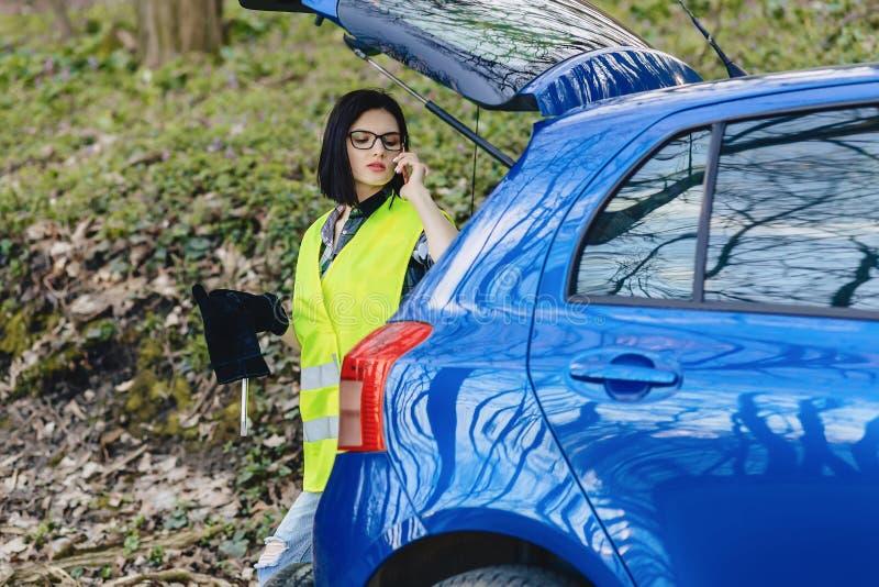 menina atrativa que fala pelo telefone perto do carro na estrada no jaque da segurança fotos de stock royalty free