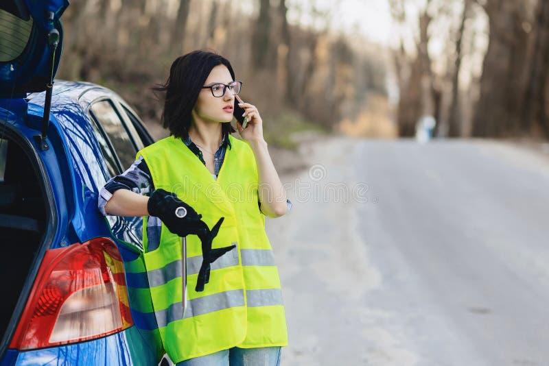 menina atrativa que fala pelo telefone perto do carro na estrada no jaque da segurança fotografia de stock royalty free