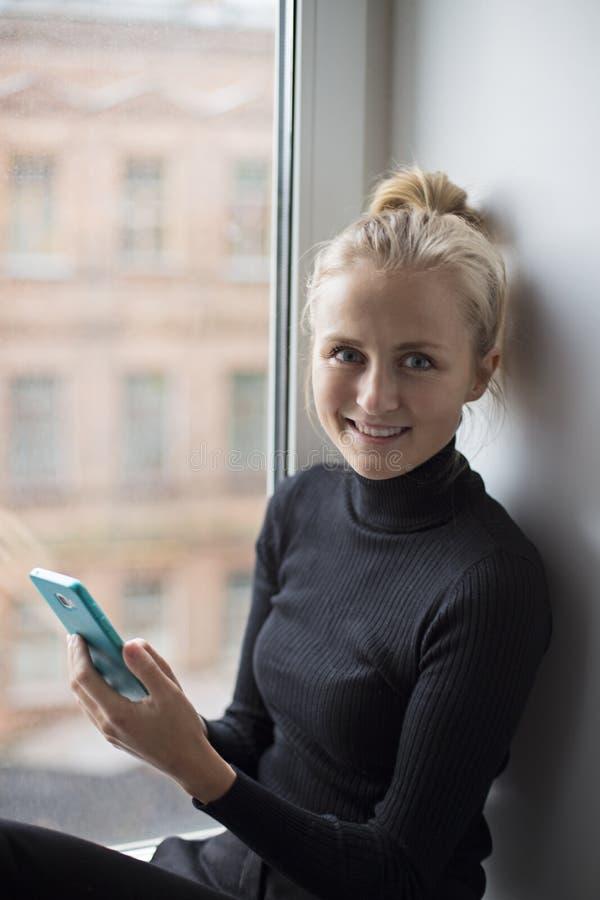 Menina atrativa que guarda um telefone em suas mãos e que olha na câmera fotografia de stock