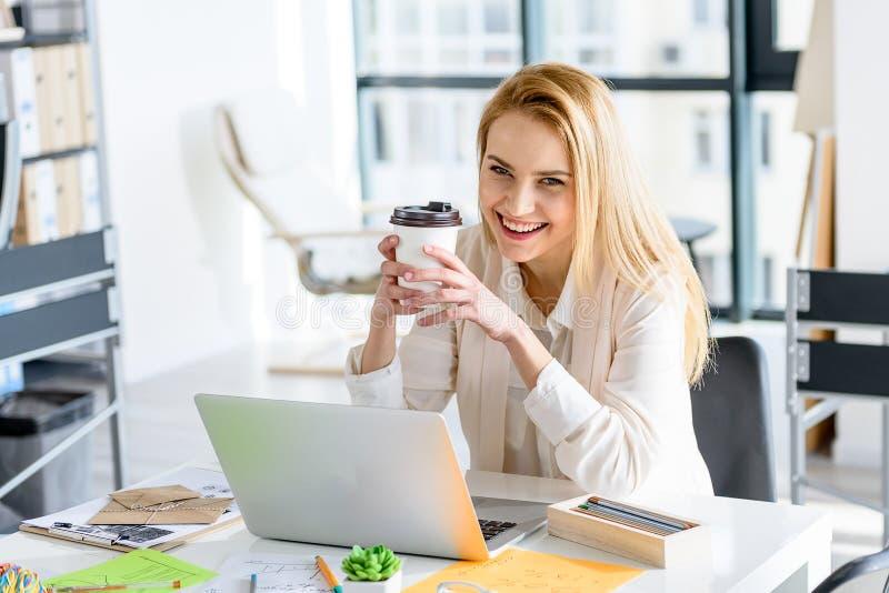 Menina atrativa que levanta com a bebida quente em sua mão foto de stock