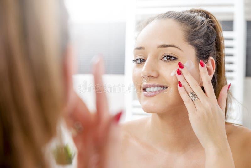 Menina atrativa que põe o creme antienvelhecimento foto de stock royalty free