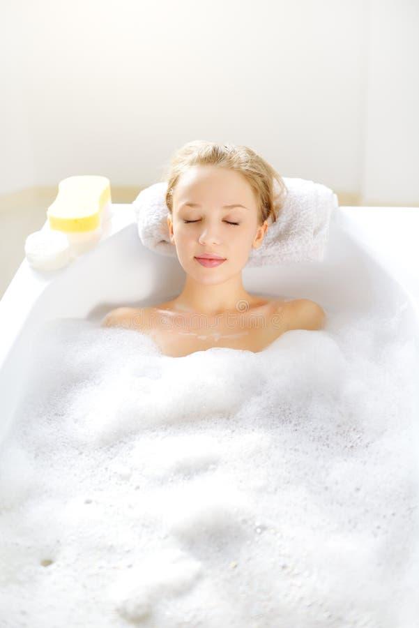 Menina atrativa que relaxa no banho imagem de stock