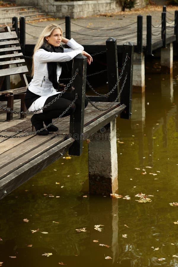 Menina atrativa que squatting pelo lago no parque fotos de stock royalty free