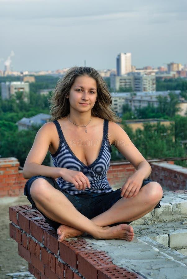 A menina atrativa relaxa no telhado fotos de stock