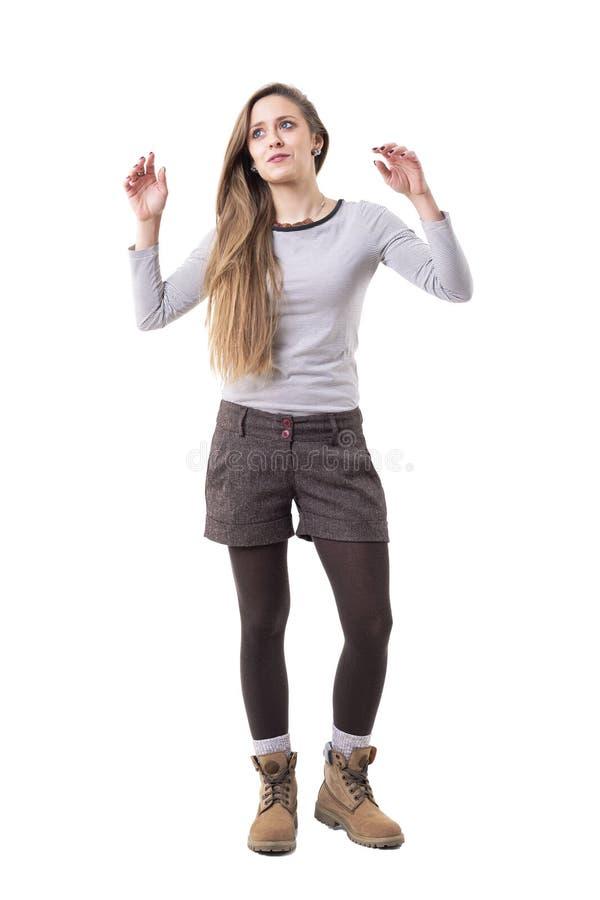 Menina autêntica espontânea cândido do moderno com os braços aumentados que olham surpreendidos acima fotografia de stock royalty free
