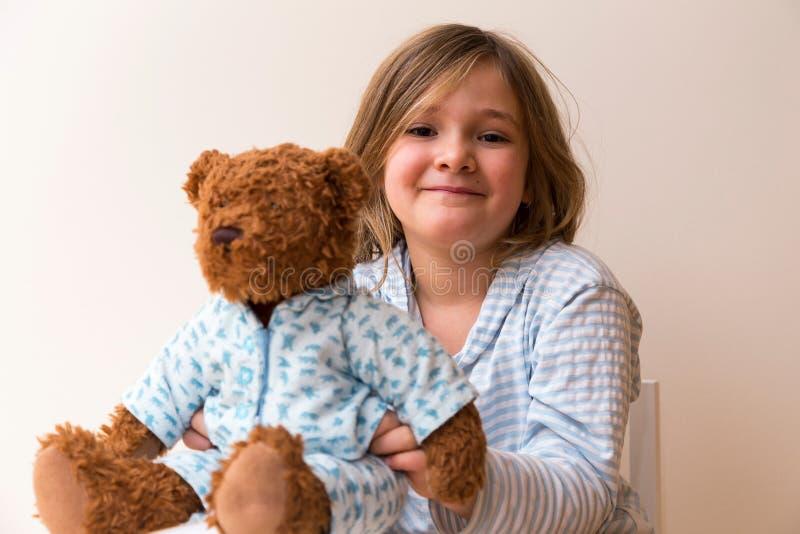 Menina bagunçado que guarda seu urso de peluche pyjama-folheado fotografia de stock royalty free