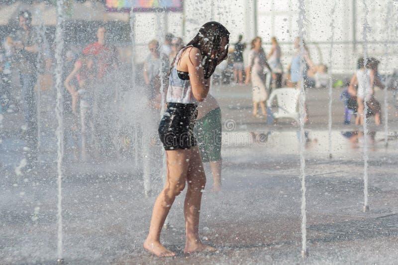 A menina banha-se na fonte no dia quente fotografia de stock royalty free