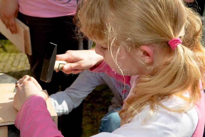 A menina bate um prego na madeira imagens de stock