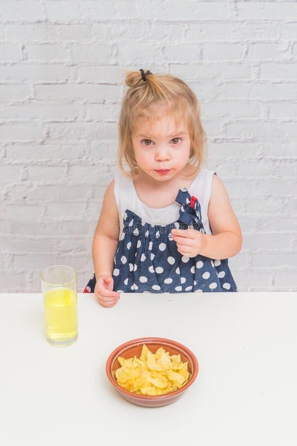 A menina, bebê que come microplaquetas de batata e que bebe a soda, não saúde imagem de stock royalty free