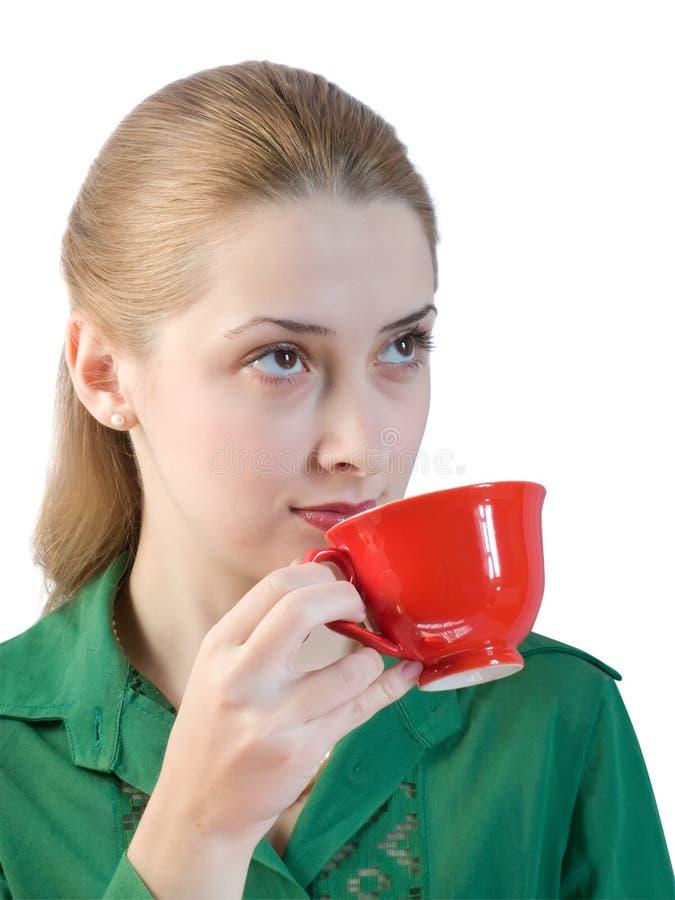 A menina bebe o chá de um copo vermelho fotos de stock royalty free